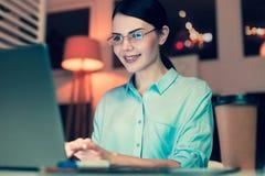 Angenäm ung kvinna som sent arbetar i kontoret Royaltyfri Foto