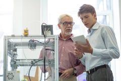 Angenäm ung man och hans kollega som kontrollerar data på minnestavlan Arkivbilder