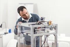 Angenäm ung man som kontrollerar arbetet av skrivaren 3D Fotografering för Bildbyråer