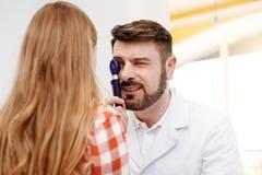 Angenäm vänlig doktor som försiktigt studerar ögon arkivfoto