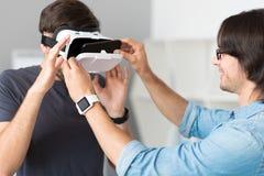 Angenäma gladlynta kollegor som testar virtuell verklighetexponeringsglas Arkivbild
