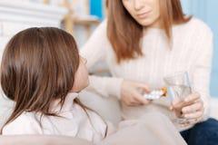 Angenämt sjukt flickasammanträde på soffan med hennes moder Fotografering för Bildbyråer