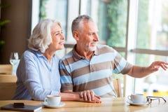 Angenehme ältere liebevolle Paare, die im Café stillstehen stockbild