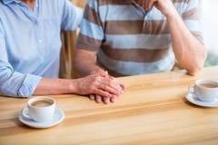 Angenehme ältere liebevolle Paare, die am Tisch sitzen stockfotos