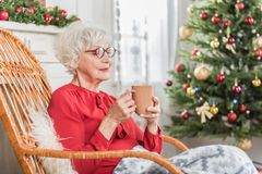 Angenehme alte Dame hält Becher im Feiertag Stockfoto