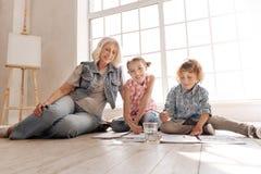 Angenehme begeisterte Kinder, die auf dem Boden sitzen Lizenzfreies Stockbild