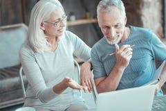Angenehme beschäftigte Paare, die an die Aufgabe in Verbindung stehen und denken stockfotografie