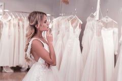 Angenehme durchdachte Braut, welche die Kleider betrachtet stockfotos