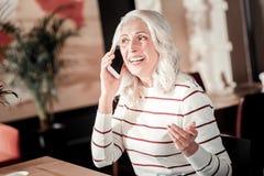 Angenehme emotionale ältere Frau, die am Telefon sitzt und spricht lizenzfreies stockbild