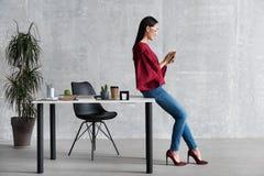 Angenehme faszinierende Geschäftsfrau hält intelligentes Gerät lizenzfreie stockbilder