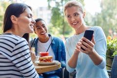 Angenehme Frau, die ihren Freunden Telefonfotos zeigt Lizenzfreies Stockfoto