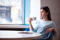 Angenehme Frau, die im Café sitzt Lizenzfreie Stockfotografie
