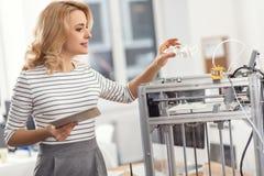 Angenehme Frau, die vor kurzem Druckteil des Hausmodells betrachtet Stockfotografie