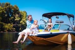 Angenehme junge Familie, die auf einem Motorboot sich entspannt stockfoto