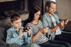 Angenehme junge Familie, die zu ihren Telefonen gewöhnt wird lizenzfreies stockfoto
