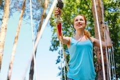 Angenehme junge Frau, die an einem Erlebnispark klettert lizenzfreie stockfotos