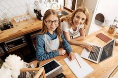 Angenehme Mutter und Tochter, die an neuen Konzepten arbeitet Lizenzfreies Stockbild