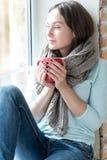 Angenehme nette Frau, die Ansicht vom Fenster genießt Stockfotos