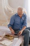Angenehmer älterer Mann, der alte Buchstaben umdreht Lizenzfreies Stockbild