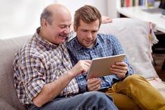 Angenehmer älterer Mann, der auf die Tablette, einen interessanten Artikel zeigend auf seinen Sohn zeigt lizenzfreies stockfoto