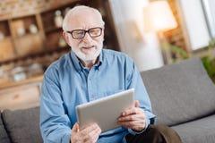 Angenehmer älterer Mann, der das Netz auf Tablette surft lizenzfreie stockfotos