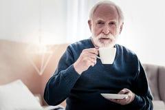 Angenehmer älterer Mann, der eine Tasse Tee hält lizenzfreie stockbilder
