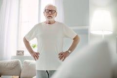 Angenehmer älterer Mann, der im Raum steht lizenzfreie stockfotos