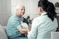 Angenehmer älterer Mann, der seinen Arm für Einspritzung sitzt und vorbereitet stockfoto