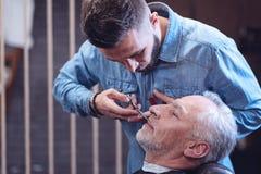 Angenehmer älterer Mann, der seinen Bart sich pflegen lässt Lizenzfreies Stockbild