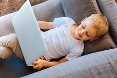 Angenehmer begeisterter Junge, der auf dem Sofa stillsteht Lizenzfreie Stockfotos