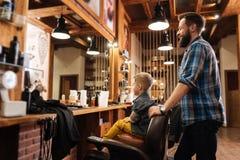Angenehmer blonder Junge, der auf dem Stuhl sitzt Lizenzfreie Stockfotografie