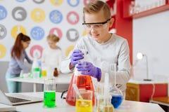 Angenehmer blonder Junge, der innere chemische Flasche schaut Lizenzfreies Stockbild