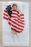 Angenehmer blonder Junge, der mit der US-Flagge bedeckt wird Stockfotografie