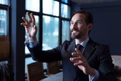 Angenehmer froher Mann, der einen virtuellen sensorischen Schirm berührt stockbilder