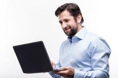 Angenehmer Geschäftsmann von mittlerem Alter, der an seinem Laptop arbeitet stockbild
