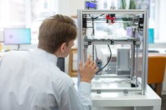 Angenehmer junger Ingenieur, der Drucker 3D in der Aktion aufpasst lizenzfreie stockfotos
