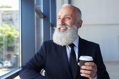 Angenehmer lächelnder Mann beim Halten des Kaffees und Fenster heraus schauen Lizenzfreie Stockfotos