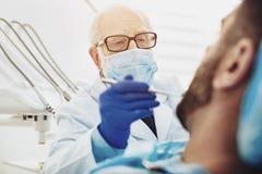 Angenehmer männlicher Zahnarzt, der Zahnfleischerkrankung behandelt lizenzfreies stockfoto