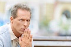 Angenehmer Mann, der auf der Bank sitzt Lizenzfreies Stockbild
