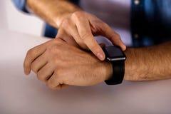 Angenehmer Mann, der seine intelligente Uhr verwendet lizenzfreies stockfoto