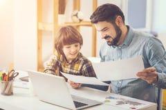 Angenehmer mitfühlender Vater, der seinem Sohn mit Schulhausarbeit hilft lizenzfreie stockfotografie