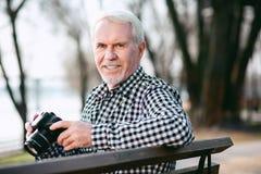 Angenehmer reifer Mann, der Fotografie lernt stockfotos