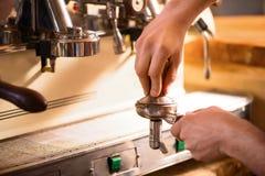 Angenehmes barista unter Verwendung der Kaffeemaschine Stockbilder