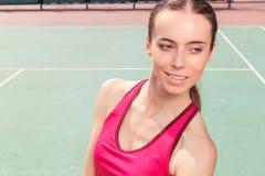 Angenehmes Mädchen, das auf Tennisplatz bleibt Lizenzfreie Stockfotografie