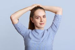 Angenehmes schauendes junges weibliches Modell stellt Pferdeschwanz, trägt gestreifte stilvolle Bluse, aufwirft gegen blauen Hint stockbilder