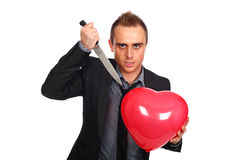 Anger. Young man holding a heart shaped balloon and a knife Royalty Free Stock Photo