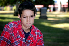 Anger. A sad angry young tween boy sitting in a cemetery with out of focus tombstones in the background. Shallow depth of field Stock Photos