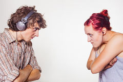 Anger. Young couple in headphones are angry at each other on a light background Stock Photography