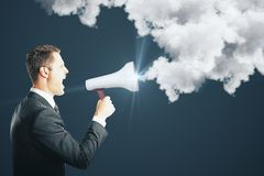 Anger and announcement concept. Side view of young businessman screaming into glowing megaphone on dark background with communication cloud. Anger and Royalty Free Stock Image