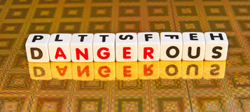 Anger is dangerous. Text ' dangerous ' in uppercase letters  inscribed on small white cubes with ' anger ' delineated in red letters, gold background Stock Photography